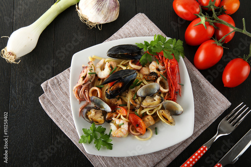 Foto  Italian pasta with seafood, mussels, clams, shrimp and squid