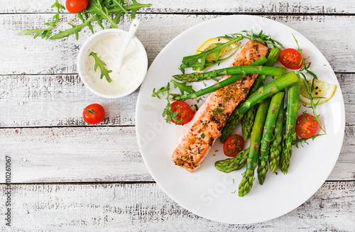 Foto auf Leinwand Fisch Baked salmon garnished with asparagus and tomatoes with herbs. Top view