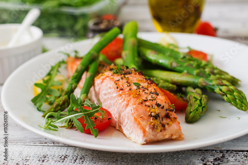 Foto Baked salmon garnished with asparagus and tomatoes with herbs