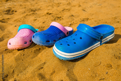 c5905dfee Crocs on the sand. three pairs of flip-flops on the beach