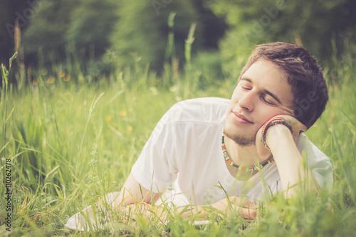 Fotografía  Junger Mann liegt im Gras, nachdenklich