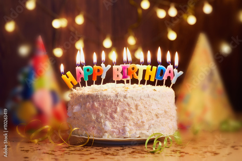 Photo  Birthday cake with candles, bright lights bokeh.
