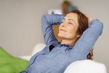Zufriedene Frau Sitzt Auf Dem Sofa Und Hat Die Augen Geschlossen