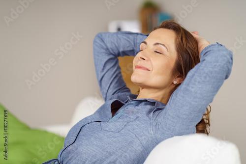 Photo  zufriedene frau sitzt auf dem sofa und hat die augen geschlossen