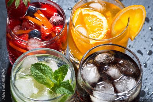 Fotografía  assortment of fresh iced fruit drinks on a dark background