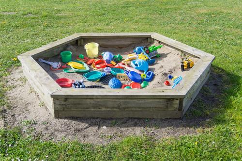 Fotografie, Obraz  Sandkasten im Garten auf der Wiese mit viel Spielzeug