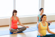 happy pregnant women exercising yoga in gym