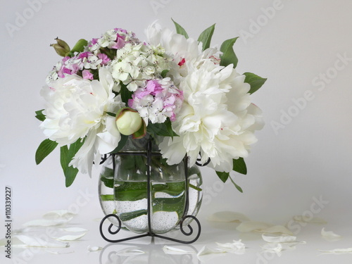 Bouquet of white peony flowers in a vase. Floral decoration with bouquet of peonies and pink carnations flowers in a vase. - 110339227