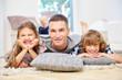 Vater und Kinder im Wohnzimmer lachen fröhlich