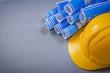 Building helmet blue rolled engineering drawings on grey backgro