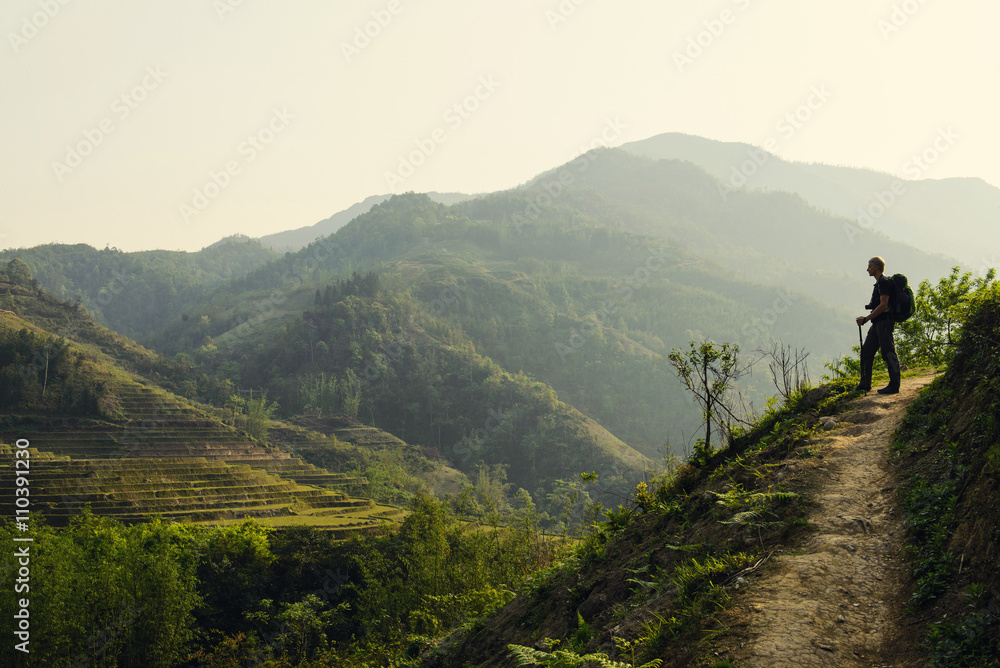 Fototapety, obrazy: Man hiking with backpack holding trekking sticks in the mountain