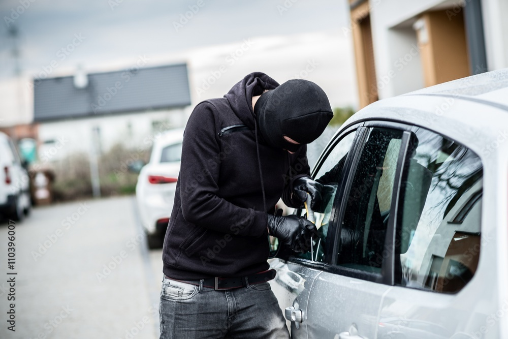 Fototapeta Car thief trying to break into a car with a screwdriver