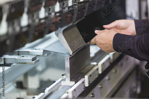 Foto op Canvas Metal operator bending metal sheet by sheet bending machine