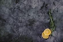 Rosemary With Sliced Lemon On Dark Stone Table
