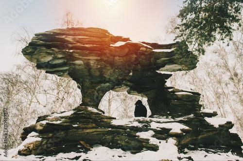Juliste Hiker sitting under rock formation in snow