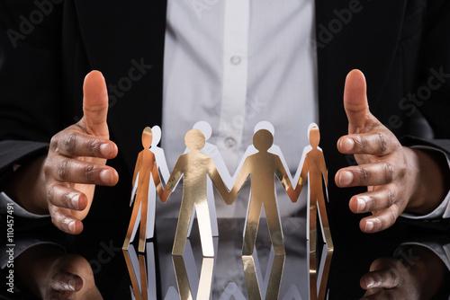 Fotografie, Obraz  Businessperson Protecting Cut-out Figures