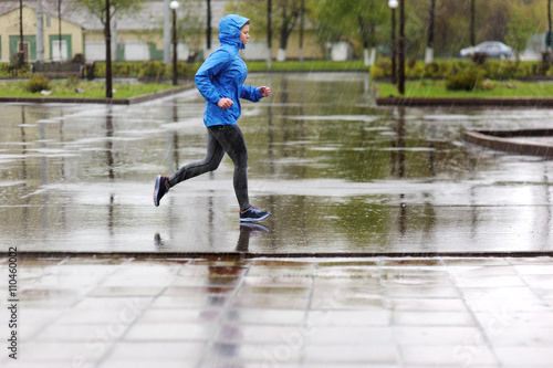 Poster Jogging Runner woman running in Park in the rain. Jogging training for m