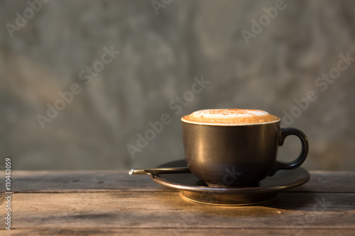 Tablou Canvas Hot cappuccino coffee cup on wooden table agent sunlight in morn