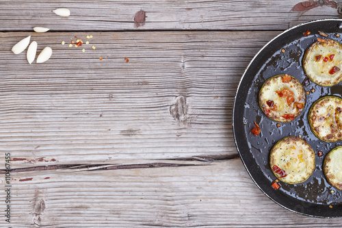 Frying pan with fried zucchini and garlic on 