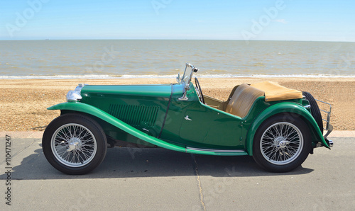 Classic Green Sports car parked on seafront promenade.