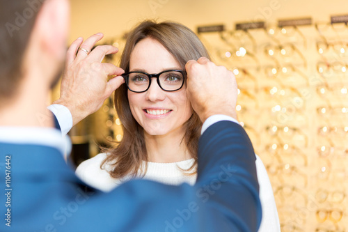 Fényképezés  Young attractive  woman testing new glasses with optician