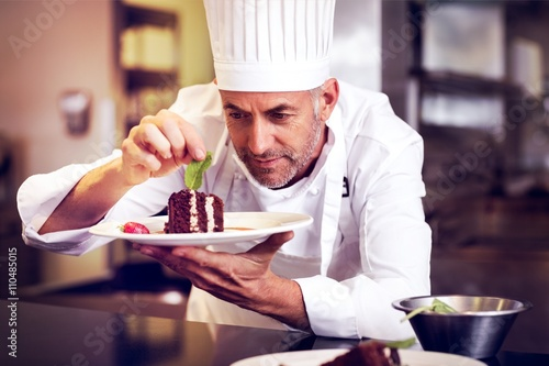 Concentrated male pastry chef decorating dessert in kitchen Tableau sur Toile
