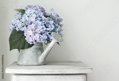 Tuinposter Hydrangea Hydrangea flowers in grunge zinc watering can on vintage wooden