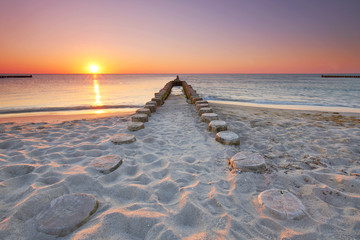 Plakat lange hölzerne Buhnen am Strand, Sonnenuntergang am Meer