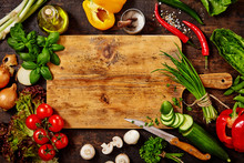 Cutting Board And Knife With Vegetables On Table