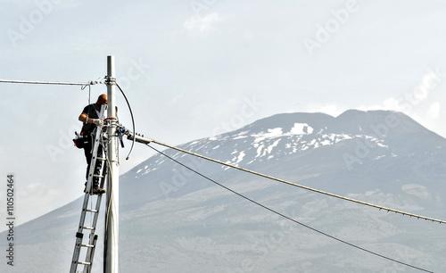 Fotografie, Obraz  elettricista uomo al lavoro, su scala con palo e cavi