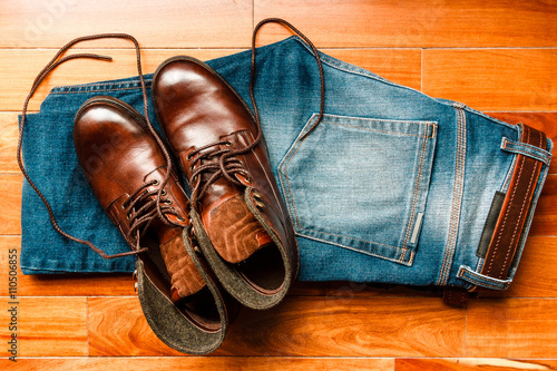 Fotografie, Obraz  Folder jeans with leather boots over wooden floor