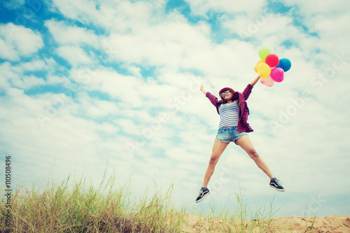 Photo  Beautiful Girl jumping with balloons on the beach