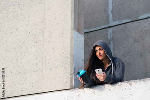 Fotografia  Fitness urban woman taking a workout rest for drinking protein shake and texting on smartphone