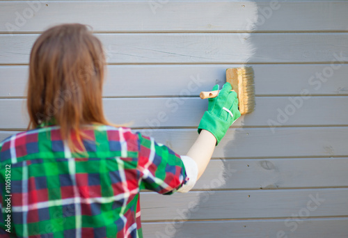 Cuadros en Lienzo Woman applying protective varnish or paint on wooden house tongue and groove cladding elevation wall