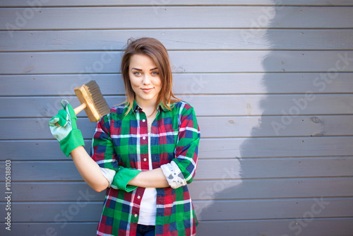 Fotografía Young working woman with paint brush, freshly painted wooden exterior wall behin