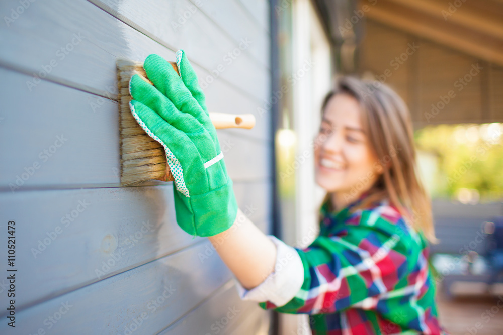 Fotografía Cheerful woman applying protective varnish or paint on wooden house tongue and groove cladding elevation wall