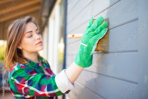 Fotomural Woman applying protective varnish or paint on wooden house tongue and groove cladding elevation wall