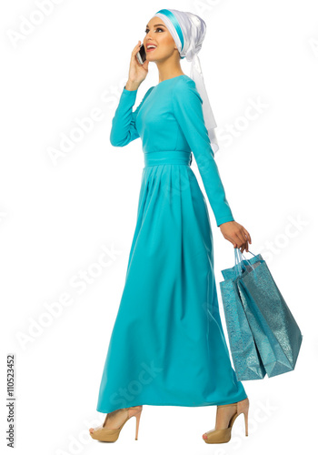 Muslim woman with mobile phone and bags