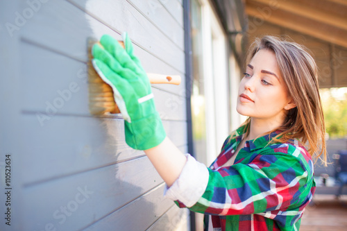 Cuadros en Lienzo Young woman applying protective varnish or paint on wooden house tongue and groove cladding elevation wall
