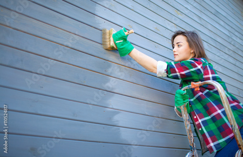 Fotomural Young woman applying protective varnish or paint on wooden house tongue and groove cladding elevation wall