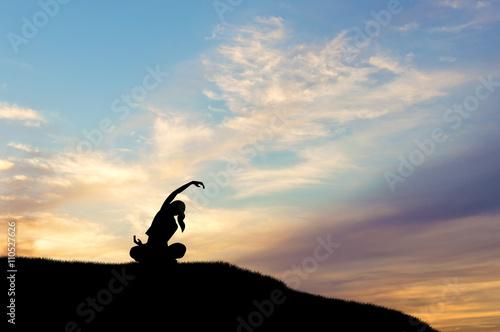 Obraz na plátně  Silhouette of woman doing yoga at sunset