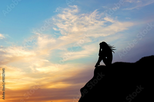 Silhouette of a woman alone on a hill at sunset