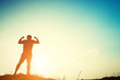 Silhouette of strong man with sunrise.
