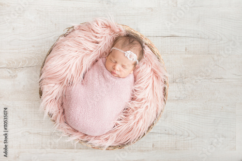 sleeping newborn baby in a basket