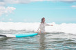 Girl on the waves with surfboard.