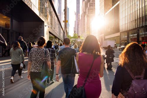 Fototapeta Ludzie chodzą od pracy przy ulicy w Nowym Jorku w czasie zachodu słońca