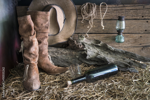 Deurstickers Retro Still life painting photography with traditional leather boots and american west rodeo brown felt cowboy hat in vintage ranch barn background