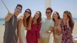 Group of young friends on vacation taking a selfie as they pose together on a balcony overlooking the beach and ocean