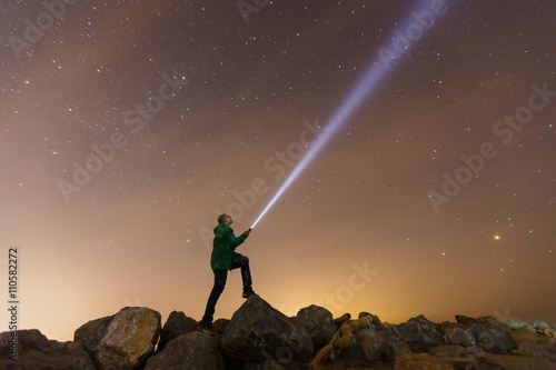 Obraz Silhouette of man with flashlight, wide stars and visible Milky way galaxy - fototapety do salonu