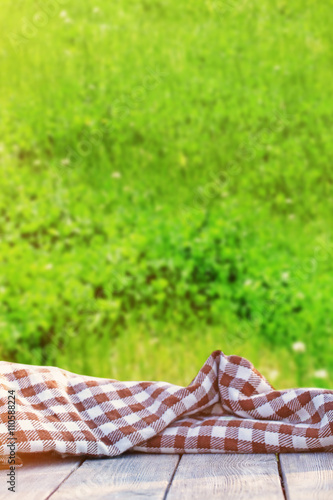 Aluminium Prints Picnic Wooden floor with blanket against green grass background
